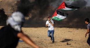 متظاهر يحمل أعلامًا فلسطينية خلال اشتباكات مع القوات الإسرائيلية على طول السياج مع إسرائيل في غزة في 27 سبتمبر