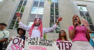 """متظاهر يرتدي زي محمد بن سلمان ويضع قناعًأ يشبهه ويرفع يده الملطخة """"بالدم"""" خارج السفارة السعودية في العاصمة واشنطن"""
