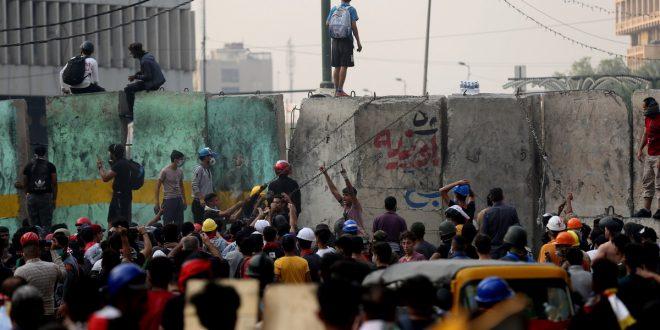 المتظاهرون يصعدون جدرانًا من الكتل الخرسانية خلال مظاهرة مناهضة للحكومة في ميدان الخلاني بوسط بغداد