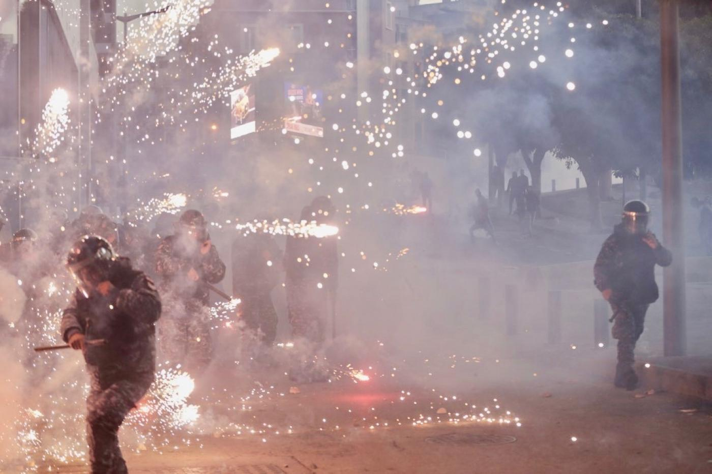 شرطة مكافحة الشغب اللبنانية وسط الألعاب النارية التي ألقاها أنصار مجموعات حزب الله وحركة أمل الشيعية اللبنانية خلال اشتباكات في بيروت يوم السبت (أ ف ب)