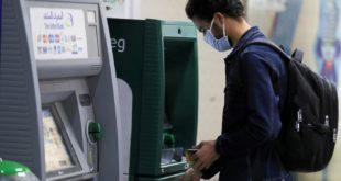 شاب يرتدي كمامة واقية يسحب أمواله من جهاز صراف آلي في محطة مترو الشهداء بالقاهرة