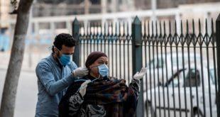 متطوع (يسار) يربط كمامة لإمرأة مصرية في شارع بالعاصمة المصرية القاهرة