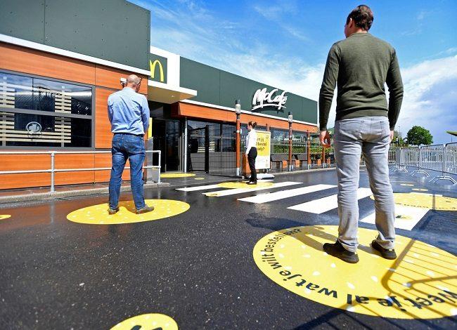 عدد من المشترين يلتزمون بالتباعد الاجتماعي أمام أحد مطاعم ماكدونالدز