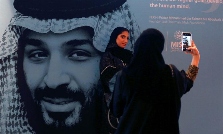 فتيات سعوديات أمام لافتة ترويجية لـ مؤسسة محمد بن سلمان الخيرية (مسك)